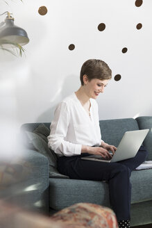 Woman using laptop on couch in modern office - FKF02345