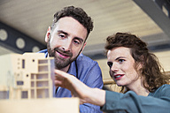 Man and woman discussing architectural model in office - FKF02357