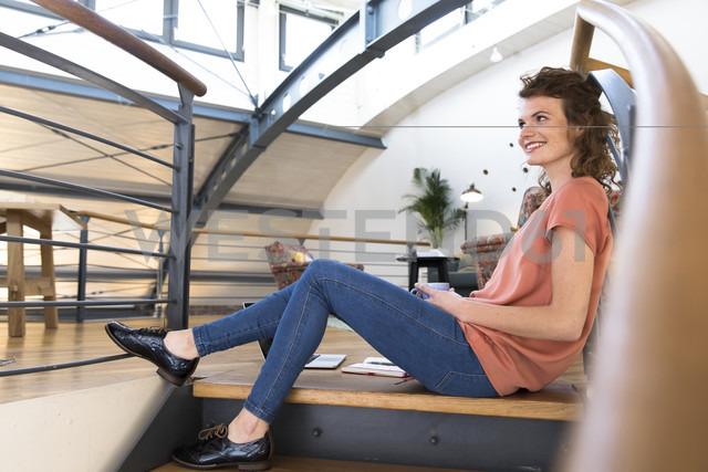 Smiling woman sitting on floor in modern office - FKF02360
