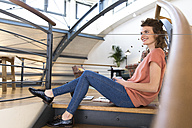 Smiling woman sitting on floor in modern office - FKF02360
