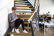 Smiling woman sitting on stairs in modern office looking at cell phone - FKF02363