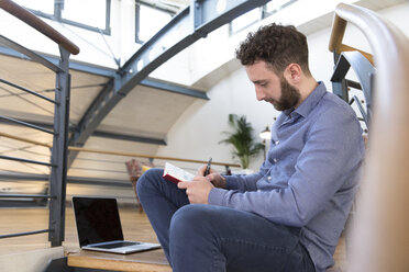 Man in modern office sitting on stairs taking notes - FKF02375
