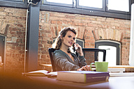 Young woman on the phone at desk in office - FKF02378