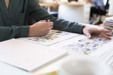 Close-up of woman at desk examining photo prints - FKF02384