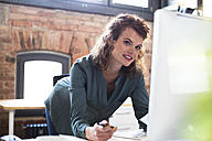 Young woman working at desk in modern office - FKF02387