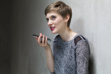 Woman using cell phone at concrete wall - FKF02396