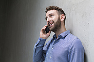 Smiling man on cell phone at concrete wall - FKF02399