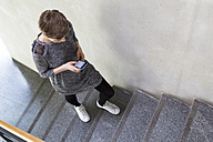 Woman walking upstairs using cell phone - FKF02402
