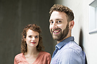 Portrait of smiling man with woman in background - FKF02408