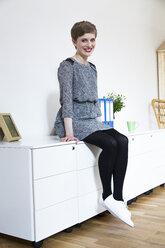Smiling woman sitting on cabinet in office - FKF02414