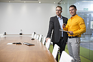 Two businessmen with tablet in office boardroom - ZEF13995