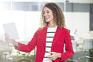 Happy businesswoman with tablet in office - ZEF14001