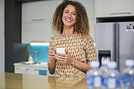 Portrait of smiling woman in office kitchen holding cup - ZEF14019