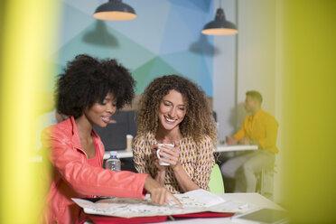 Two women talking in office lounge - ZEF14022