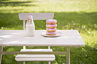 Stack of donuts and milk bottle on garden table - LVF06193