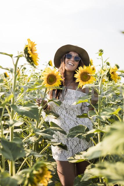 Happy woman in a sunflower field - MAUF01073
