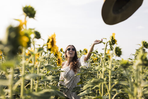 Happy woman in a sunflower field - MAUF01076