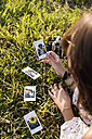 Woman lying in a field looking at instant photos of herself - MAUF01079