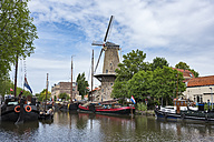 Netherlands, Gouda, harbor with traditional sailing ships and wind mill - ELF01849