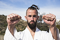 Portrait of man doing martial arts pose outdoors - ABZF02115