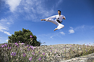 Man doing a jump kick during a martial arts training - ABZF02118