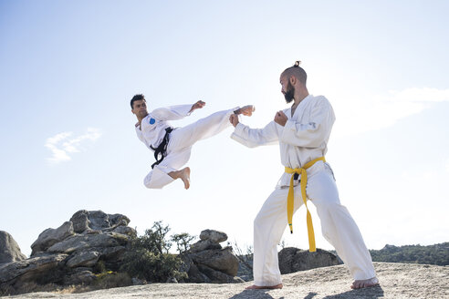 Man doing a jump kick during a martial arts combat - ABZF02121