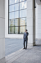 Mature businessman on cell phone outside office building - RORF00865