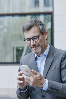 Smiling mature businessman using cell phone - RORF00868