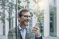 Smiling mature businessman using cell phone - RORF00871