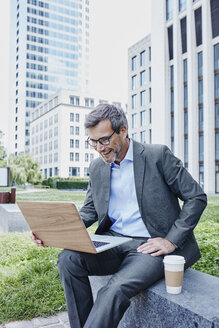 Happy mature businessman outdoors with laptop and takeaway coffee - RORF00883