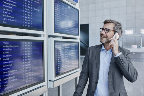 Businessman with cell phone at timetable at the airport - RORF00889