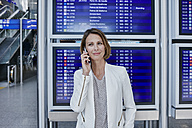 Businesswoman with cell phone at timetable at the airport - RORF00892