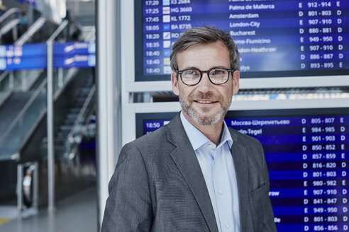 Smiling businessman at timetable at the airport - RORF00895