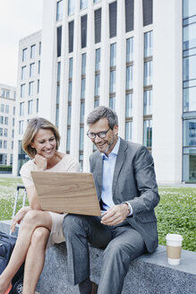 Happy businesswoman and businessman sharing laptop outdoors - RORF00898