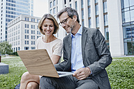 Smiling businesswoman and businessman sharing laptop outdoors - RORF00901