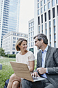 Smiling businesswoman and businessman sharing laptop outdoors - RORF00904