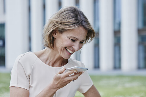 Happy businesswoman using cell phone outdoors - RORF00907