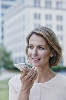 Businesswoman using cell phone outdoors - RORF00910