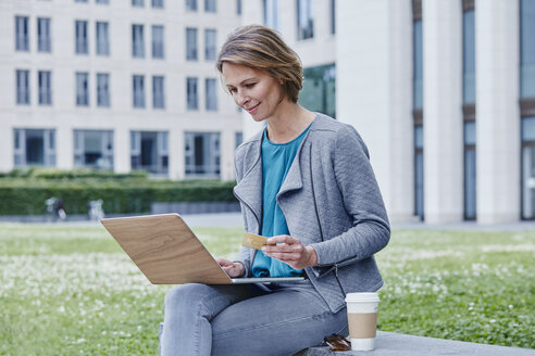 Woman outdoors with laptop, credit card and takeaway coffee - RORF00934