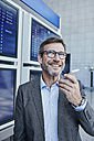 Smiling businessman with cell phone at timetable at the airport - RORF00937
