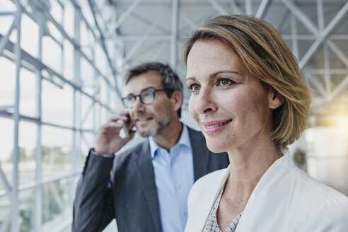 Smiling businesswoman and businessman on cell phone at the airport - RORF00943