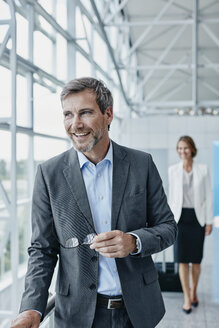 Smiling businessman and businesswoman at the airport - RORF00946