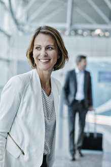 Smiling businesswoman at the airport looking sideways - RORF00949