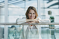 Portrait of smiling businesswoman leaning on railing at the airport - RORF00958