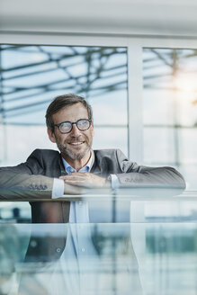 Happy businessman leaning on railing at the airport - RORF00961