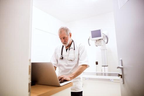 Senior vet using laptop in clinic - HAPF01704