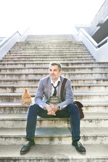 Confident businessman in the city sitting on stairs - HAPF01710