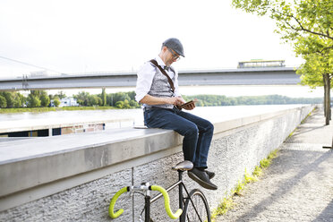 Businessman with bicycle and tablet at the riverside - HAPF01725