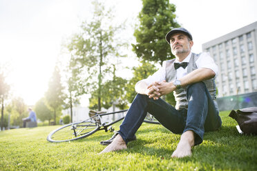 Mature businessman with bicycle in the city park sitting on grass - HAPF01728