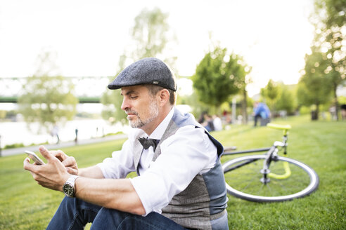 Confident mature businessman with bicycle and smartphone in the city park sitting on grass - HAPF01731